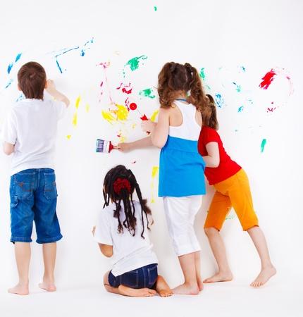 niños pintando: Cuatro elemental de años a niños pintando la pared