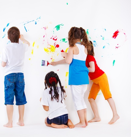 children painting: Four elementary aged kids painting  wall