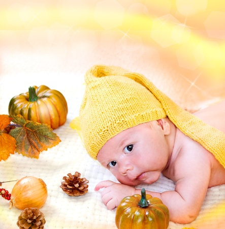Sweet newborn baby boy among autumn harvest photo
