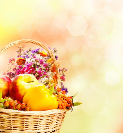 Autumn basket over yellow and orange background photo