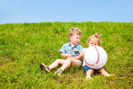 Two toddler friends sitting on the grass with a large ball Stock Photo - 10427976