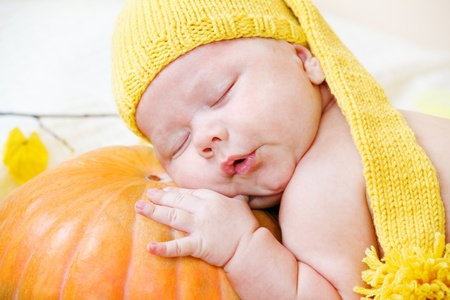 Portrait of a baby in yellow hat using pumpkin as a pillow photo