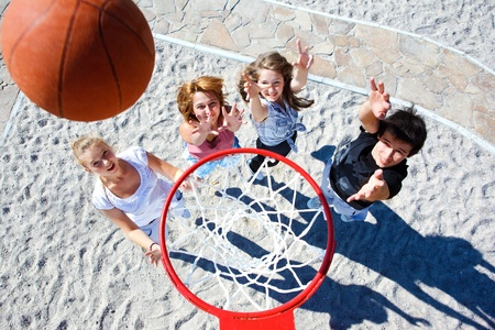 Teenagers team playing street basketball photo