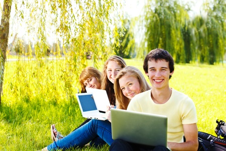 Four happy high school students with laptops photo