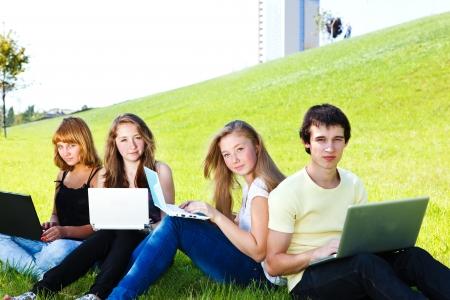 Teens with laptops, working outdoors photo