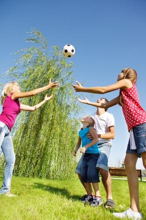 niños jugando en el parque: Familia feliz atrapando la pelota en el Parque