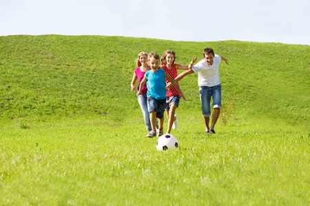 kids' soccer: Parents and kids running to the ball Stock Photo