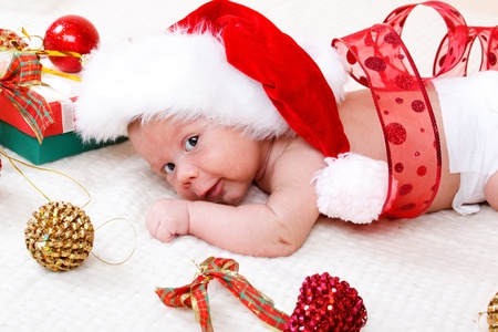Sweet baby in Christmas hat decorated with red ribbon photo