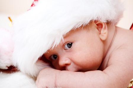 Portrait of a lovely Santa baby looking from the huge hat photo