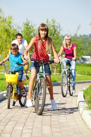 Lovely active family of four riding bicycles in park photo