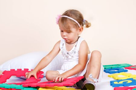 Toddler girl playing with soft puzzles Stock Photo - 10624248