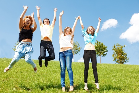 Four cheerful teenage friends jumping