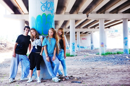 Teenagers standing at the column marked with graffiti photo