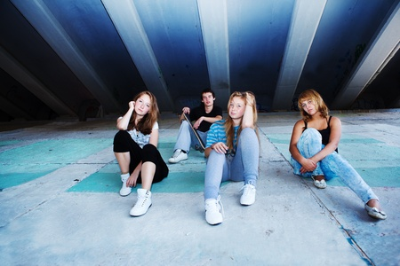 Four teenage friends sitting on concrete slabs photo
