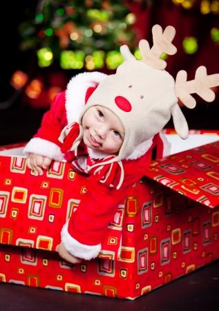 baby kerst: Baby jongen zat in een grote geschenkdoos Stockfoto
