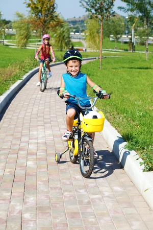 weekend activities: Cheerful school aged boy cycling, his sister behind him Stock Photo