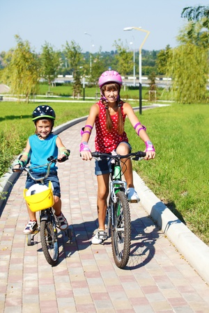 Two cheerful kids riding bikes in park photo