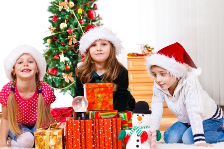 Three lovely school aged kids sit beside Christmas presents photo