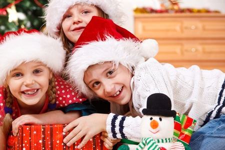 Portrait of cheerful kids in Christmas hats photo
