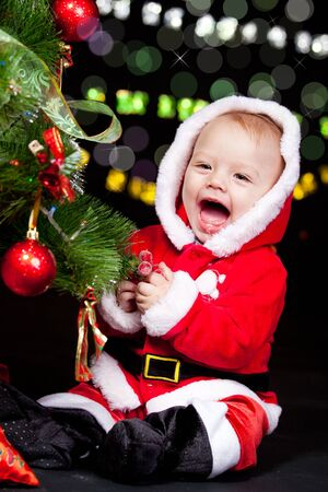 A sweet emotional Santa helper decorating Christmas tree photo