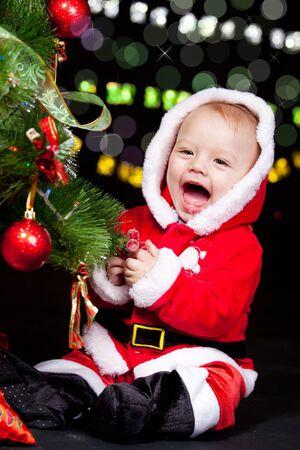 A sweet emotional Santa helper decorating Christmas tree Stock Photo - 10661646