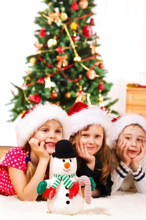 baby kerst: Een sneeuwpop en drie kinderen op de achtergrond Stockfoto