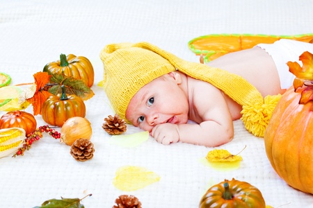 Newborn baby lying amongst leaves and vegetables photo