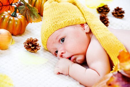 Lovely infant in yellow hat lying among autumnal leaves and pumpkins Stock Photo - 10661668