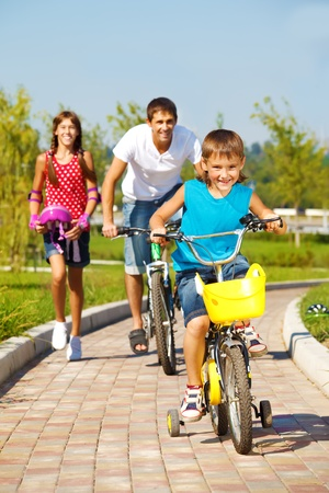School aged boy and his father cycling, cheerful girl running behind  photo