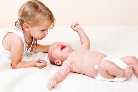 niño llorando: Niña niño mirando su hermano recién nacido llorando
