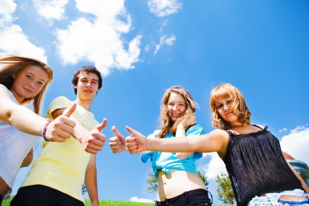 Smiling teens showing thumbs up photo