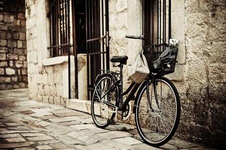 bicicleta retro: Antigua bicicleta con canasta y bolsa, estacionado en la calle estrecha Guijarro