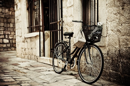 Old bicycle with basket and shopping bag, parked in the narrow cobble street photo