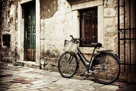 Bicycle with a shopping bag on handle bar, left beside old stone wall photo