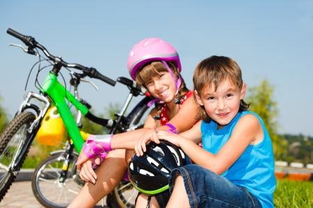 Boy and his sister in protective cycling helmets sit on grass photo