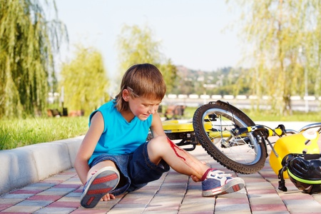 hemorragias: Ni�o llorando con una lesi�n sangrante sentado al lado de la moto que �l ha ca�do desde Foto de archivo