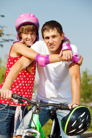 Portrait of a cheerful girl in protective sportswear and her dad on bycicle photo