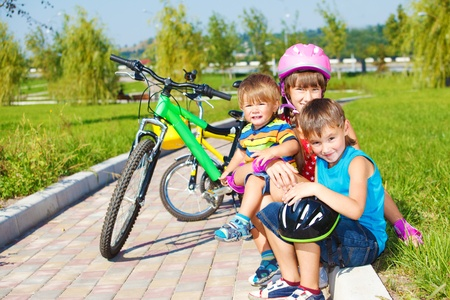 weekend activity: Siblings sitting on grass, their bikes stand behind