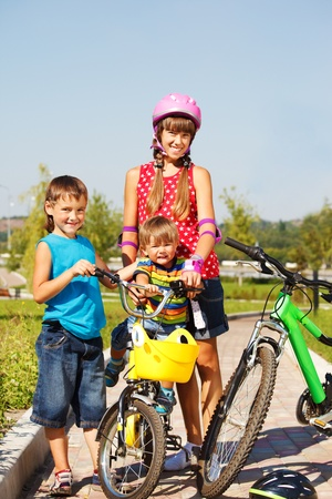 Sister and junior brothers in park, with bicycles photo