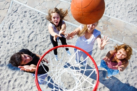 Teenagers throwing ball to the hoop photo