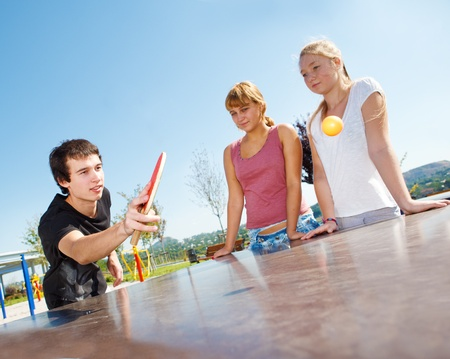 Guy playing ping pong, his friends wtaching