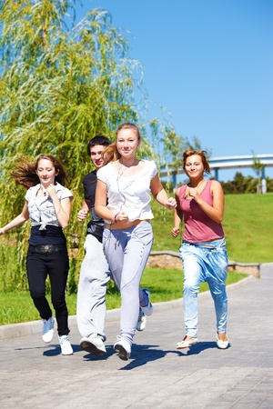 Teenage friends jogging in city park photo