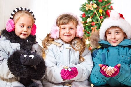 outwear: Three friends in outwear holding snow in hands Stock Photo