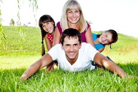 Excited family lying on grass photo