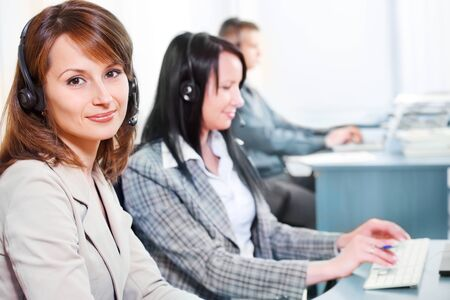 Woman with headset on, and her colleagues working in the background photo