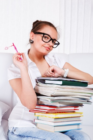 Girl in glasses keeping several books on knees  photo