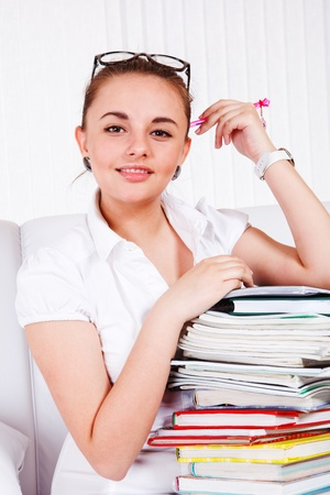 Portrait of a teen with pile of textbooks photo