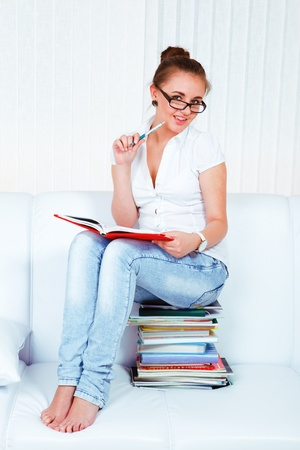 Smiling teenage girl sitting on the books stack photo