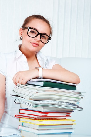Young woman in glasses and with books on her knees looking into camera photo