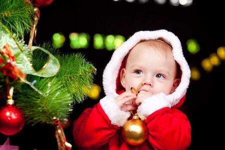 Portrait of a sweet baby boy beside Christmas tree photo